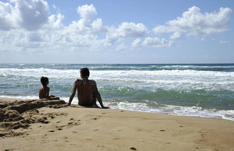 Father and son playing on the beach at the sunset time. Concept of friendly family stock photo