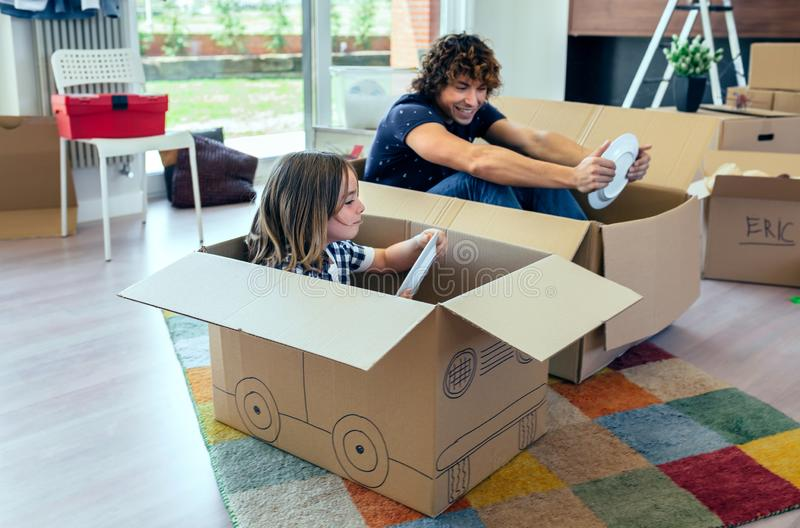 Father and son playing car racing with cardboard boxes stock image