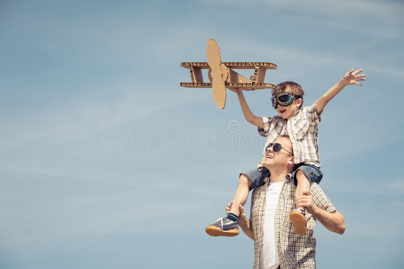 Father and son playing with cardboard toy airplane in the park a. T the day time. Concept of friendly family. People having fun outdoors. Picture made on the royalty free stock photography