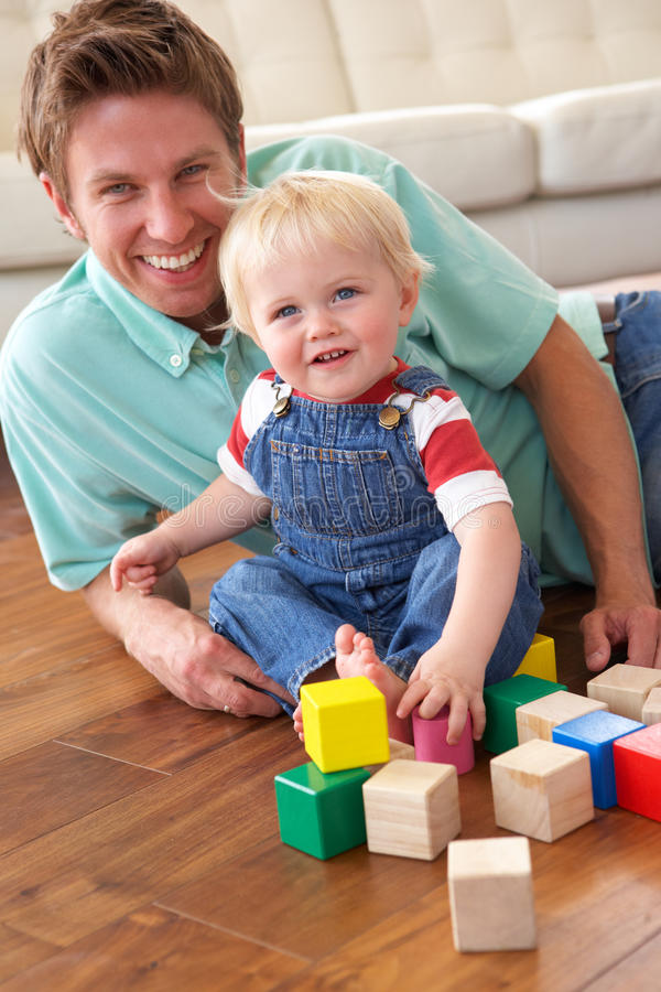 Father And Son Playing With Coloured Blocks At Hom royalty free stock photography