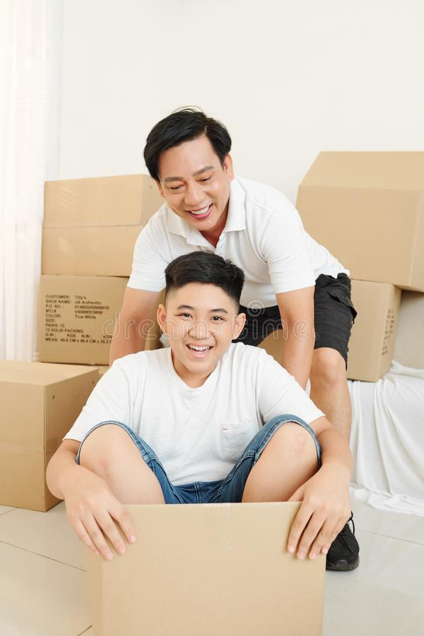 Father and son playing empty boxes stock images
