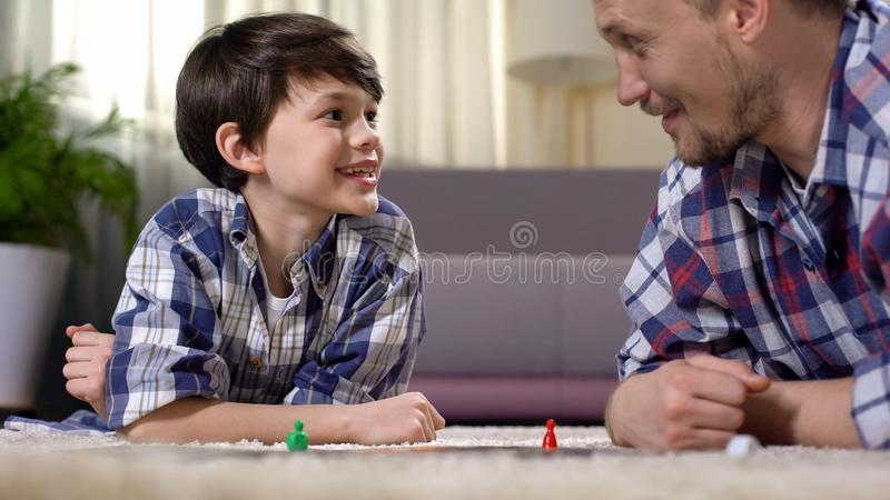 Father and son playing exciting board game, parent developing boys skills stock photo