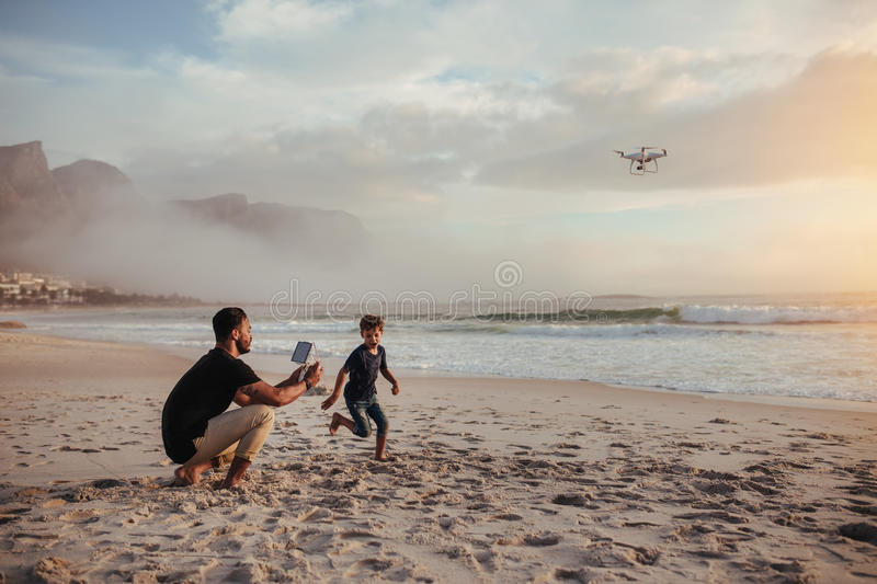 Father and son playing with flying drone on beach stock photography