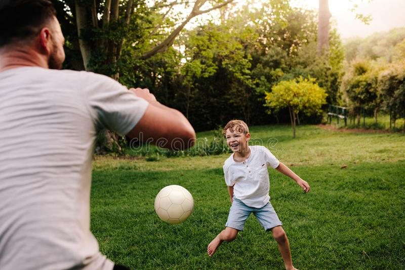 Father and son playing football in backyard garden. Happy little boy playing football with his father stock photography