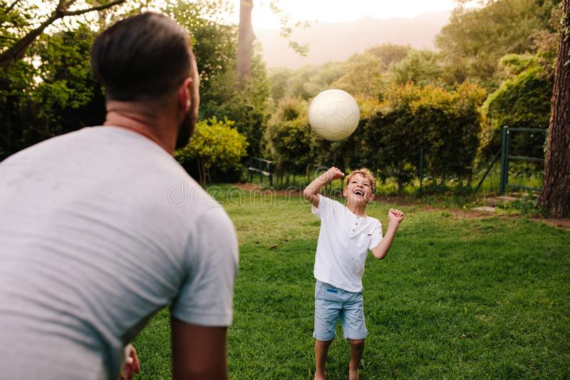 Father and son playing with a football. In backyard garden. Happy little boy passing ball to his father royalty free stock photography