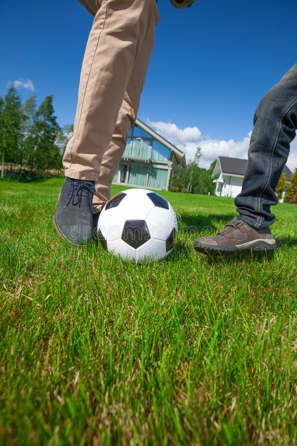 Father and son playing football. Cheerful father and son playing football on the backyard lawn near their house stock photography