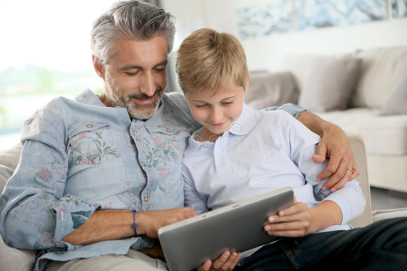 Father and son playing games on tablet stock image
