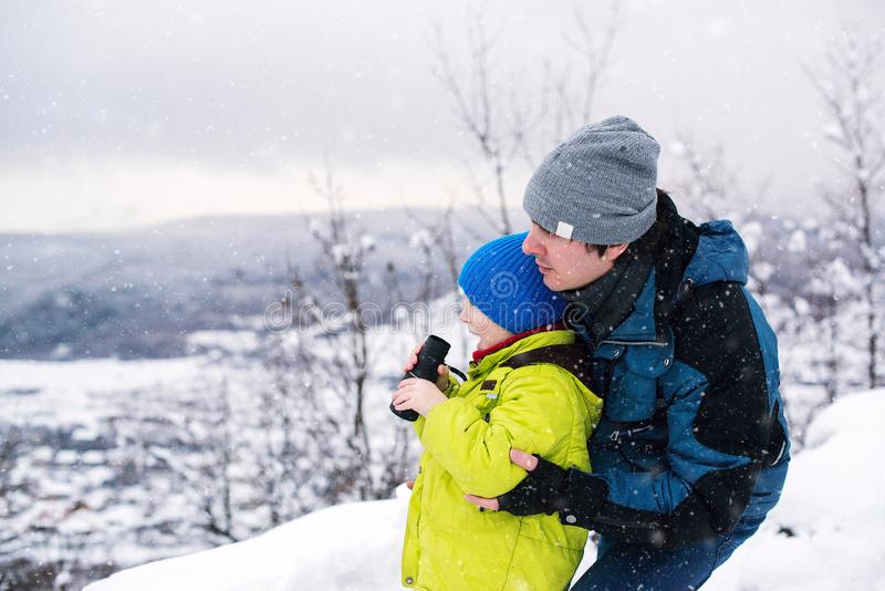 Father and son playing outdoors in winter. Kid looking to monocular. Winter outdoors game. Family winter holidays royalty free stock photo