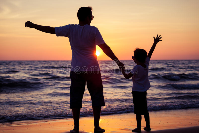 Father and son playing in the park at the sunset time. People ha. Ving fun on the beach. Concept of friendly family and of summer vacation royalty free stock images