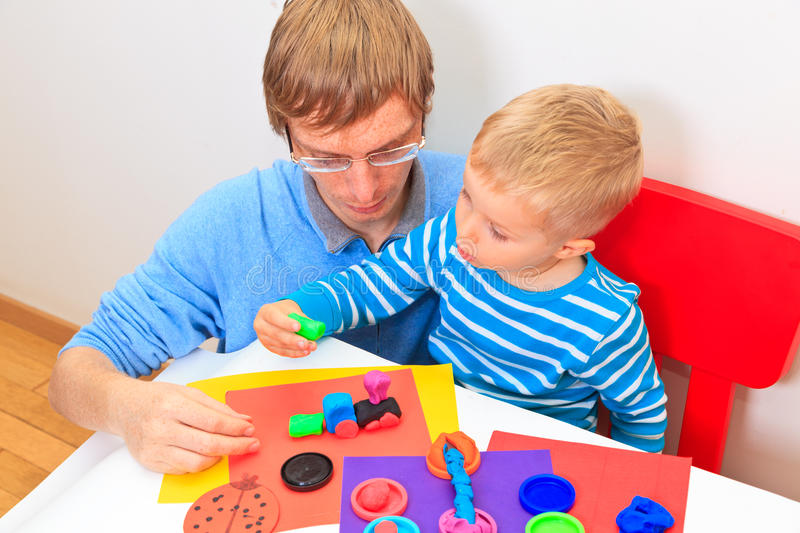 Father and son playing with plasticine. Early learning and daycare concept stock photos