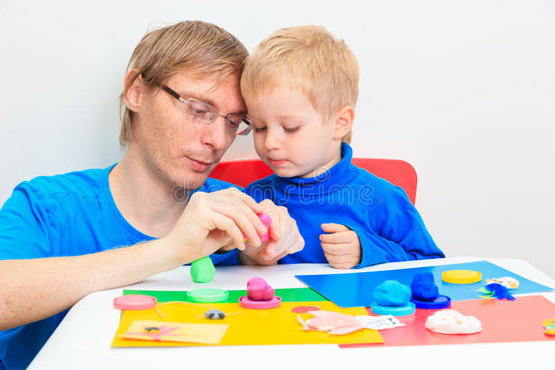 Father and son playing with plasticine. Early learning and daycare concept stock image