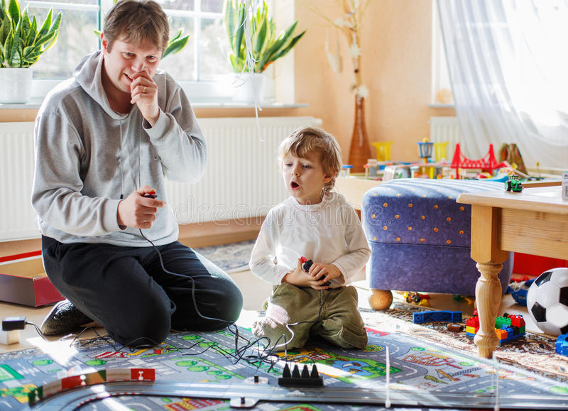 Father and son playing with racing cars on racetrack, indoors, t. Ogether stock images
