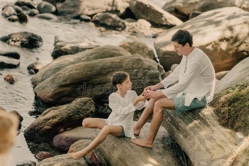 Father and son are playing on rocks royalty free stock photos