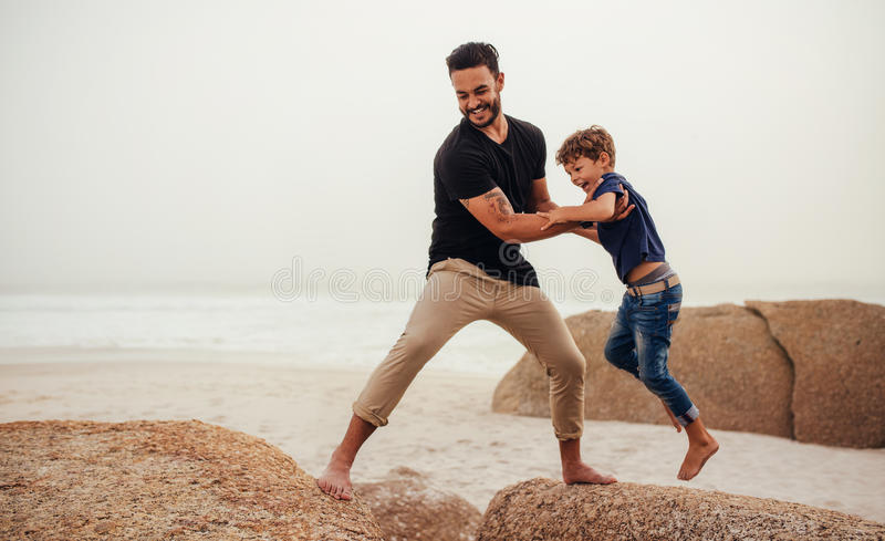 Father and son playing on the rocky sea shore royalty free stock image
