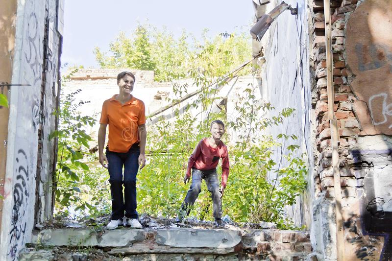 Father and son are playing through ruins stock photography