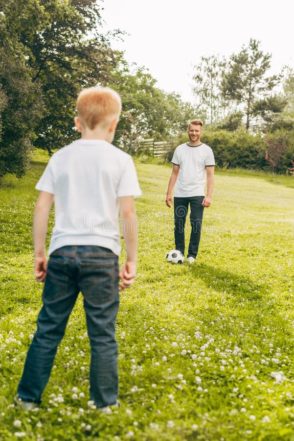 Father and son playing with soccer ball on green lawn. In park royalty free stock images