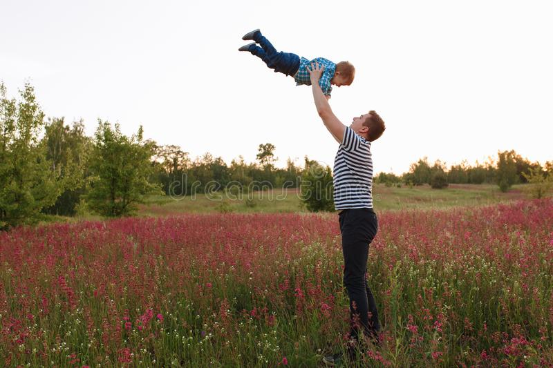 Father and son playing in the spring field at the sunset time. People having fun on the field. Concept of friendly royalty free stock photo