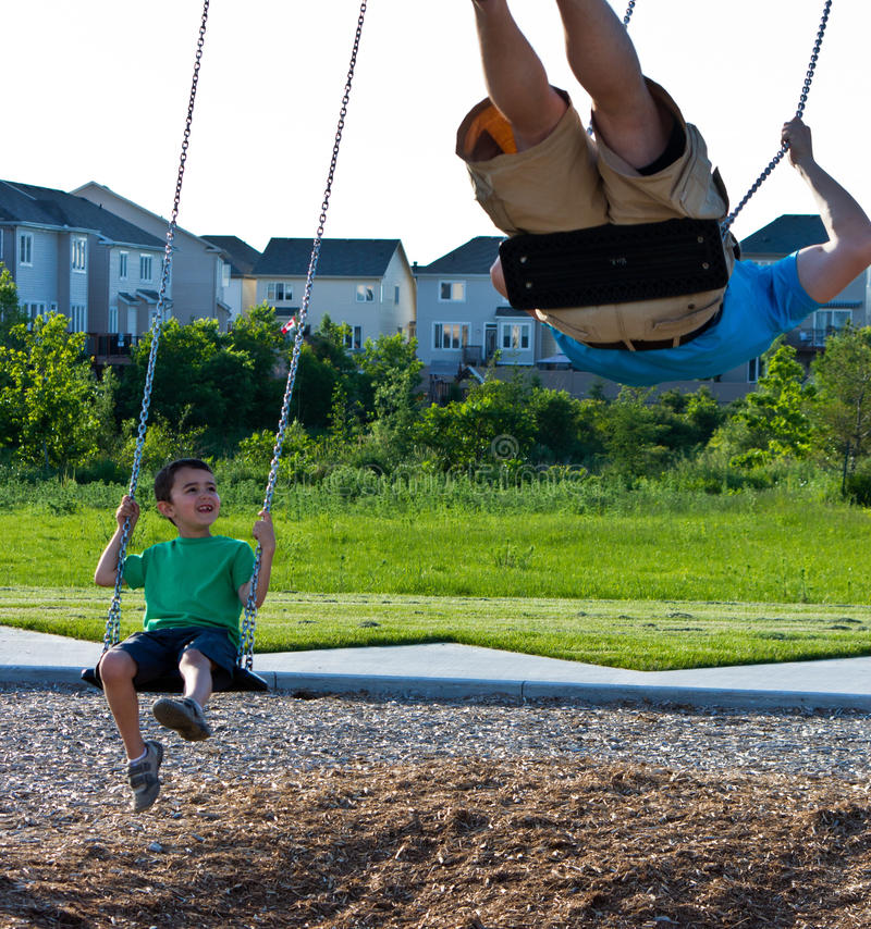 Father and son playing on the swing set at the playground royalty free stock image