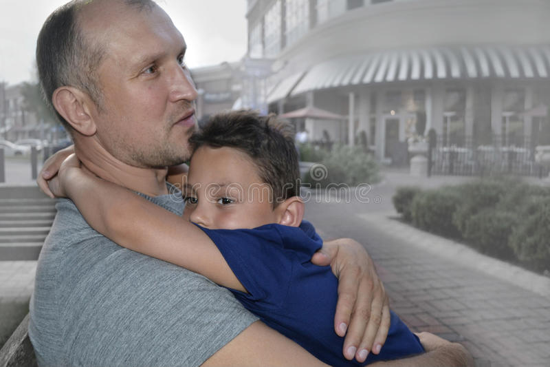 Father and son. Portrait of the father and son hugging daddys neck with city on the background royalty free stock photos