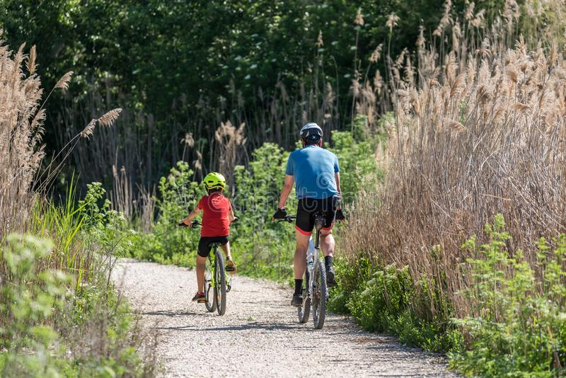 Father and son practicing sport by bicycle royalty free stock photos