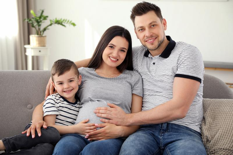 Father, son and pregnant mother spending time together. Family time. Father, son and pregnant mother spending time together on sofa at home. Family time stock photos