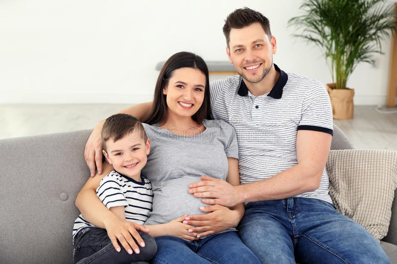 Father, son and pregnant mother spending time together on sofa. Family time. Father, son and pregnant mother spending time together on sofa at home. Family time stock photo