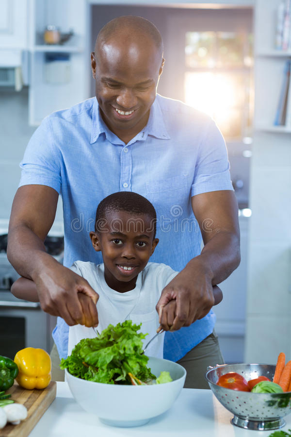 Father and son preparing food. In kitchen royalty free stock photos