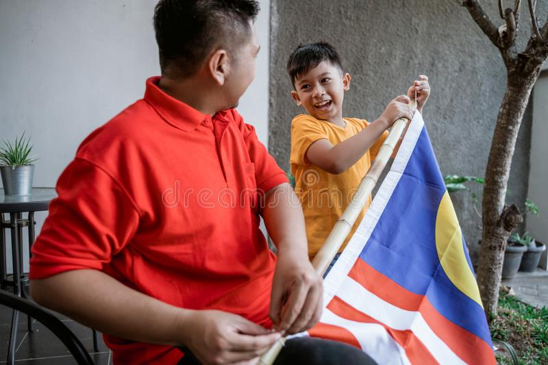 Father and son preparing malaysia flag on independence day stock image