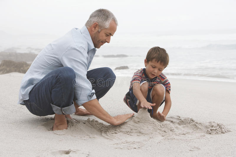 Father And Son Preparing Sand Castle Stock Image