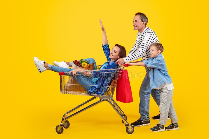 Father and son pushing shopping cart with mother stock photography