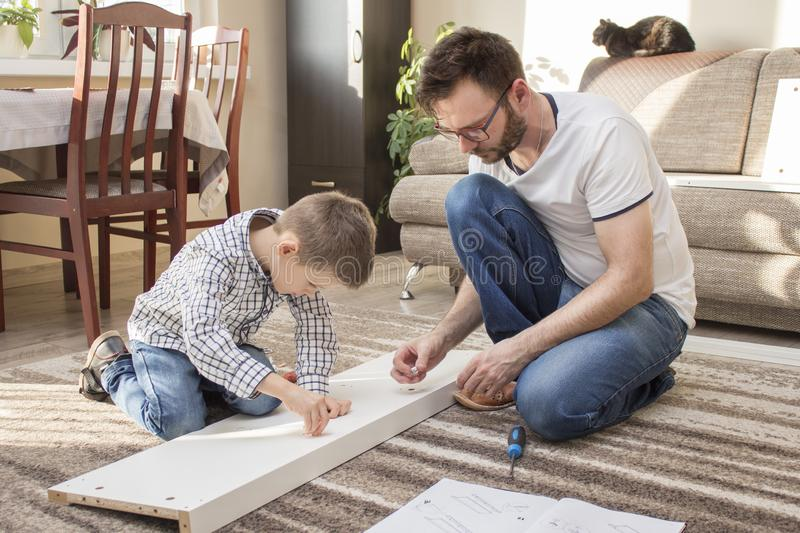 Father and son put together furniture. The father gives his son elements and the boy puts them in the right places. stock photography