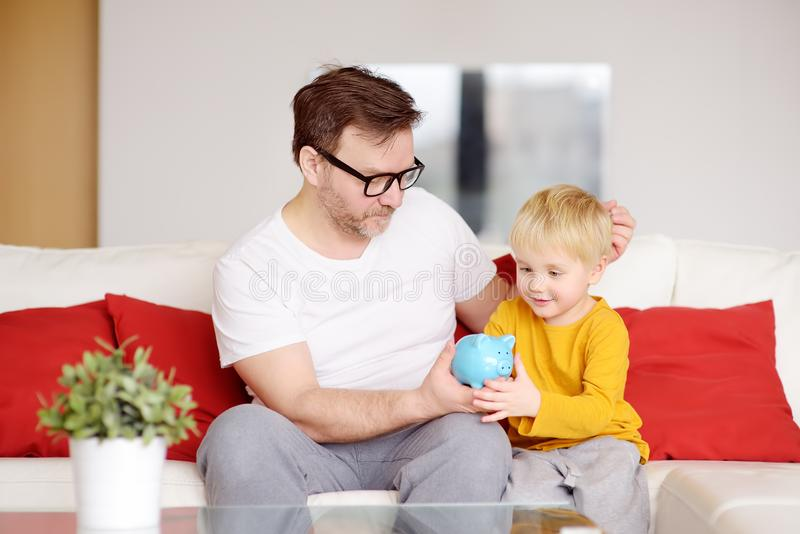 Father and son putting coin into piggy bank. Education of children in financial literacy. Quality family time stock images