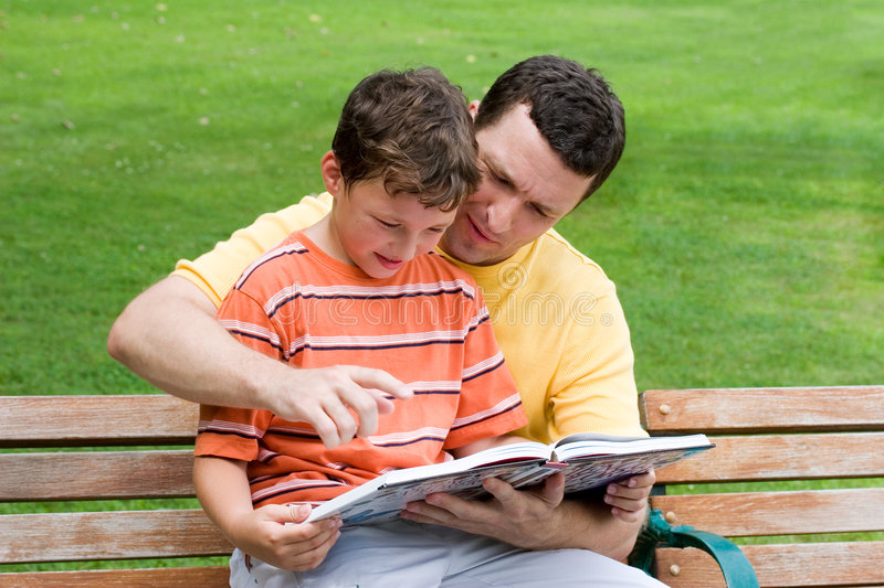 Father and son reading stock photo