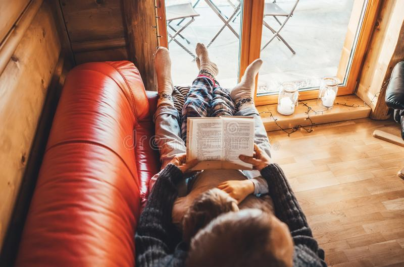 Father and son reading book together lying on the cozy sofa in warm country house. Reading to kids top view concept image royalty free stock images