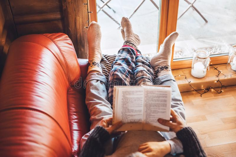 Father and son reading book together lying on the cozy sofa in warm country house. Reading to kids top view concept image royalty free stock photos