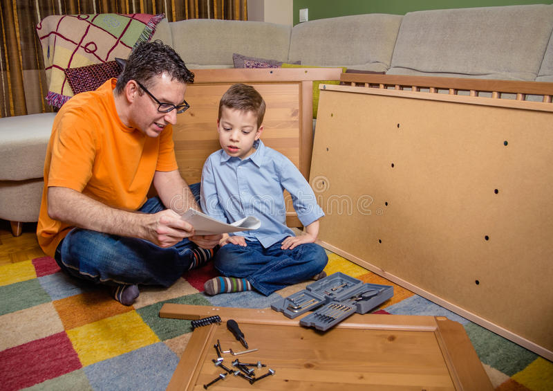 Father and son reading instructions to assemble. Portrait of father and son with tools reading the instructions to assemble a new furniture for home. Family royalty free stock photo