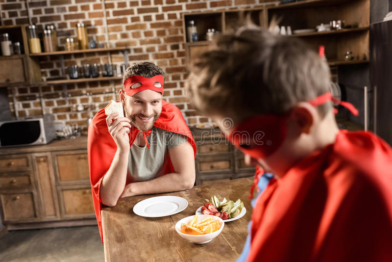 Father and son in red superhero costumes eating in kitchen royalty free stock photos