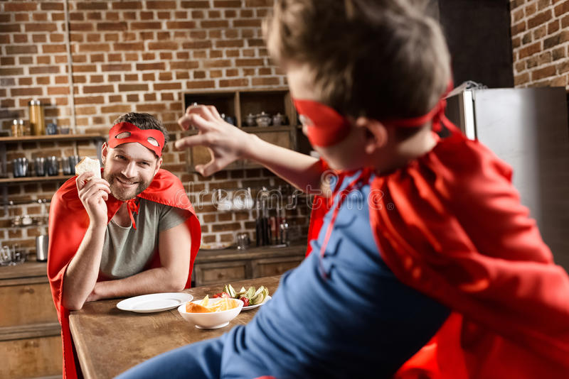 Father and son in red superhero costumes eating in kitchen royalty free stock photo