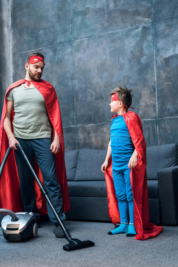 Father and son in red superhero costumes vacuuming carpet stock image