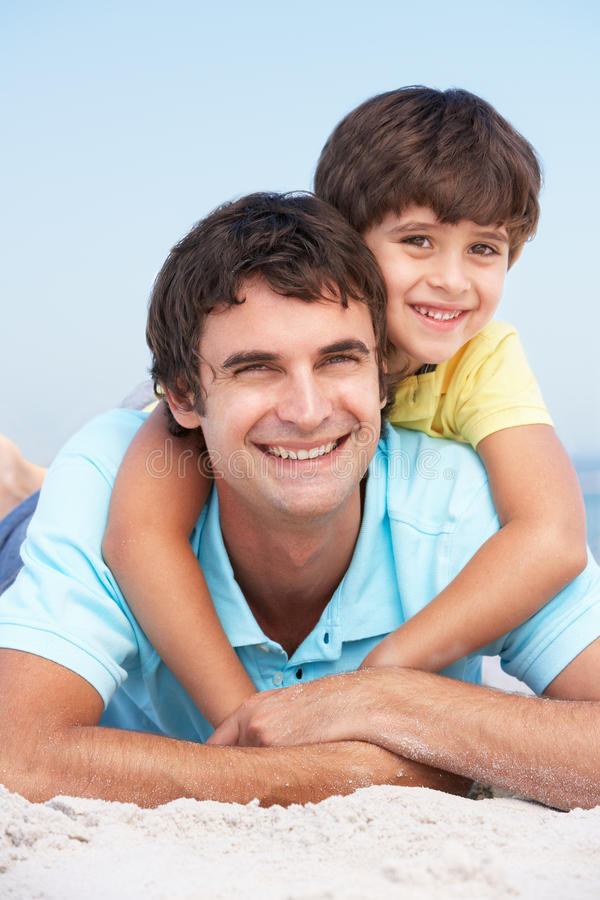 Father And Son Relaxing On Beach Holiday royalty free stock photos