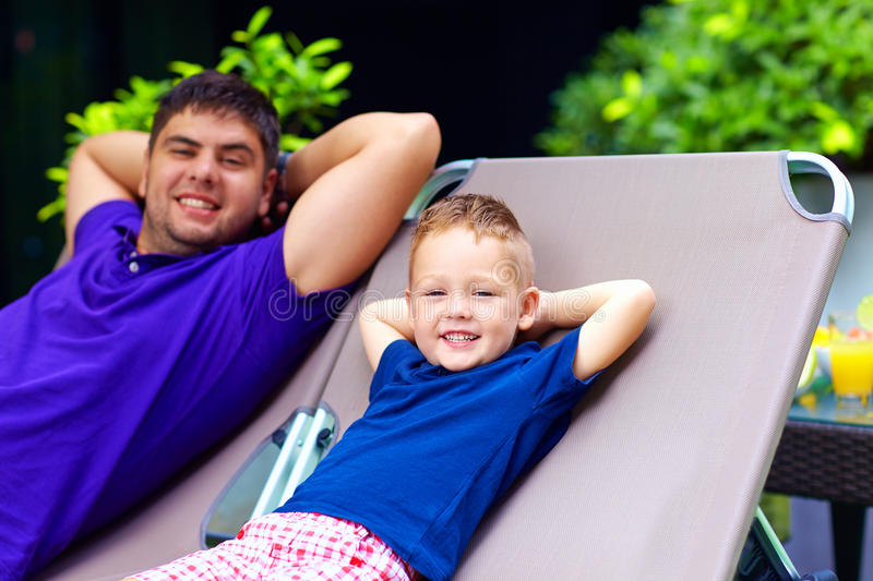 Father and son relaxing on deckchair on vacation. Happy father and son relaxing on deckchair on vacation royalty free stock photography