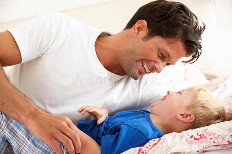 Download Father And Son Relaxing Together In Bed Stock Image - Image: 26615997