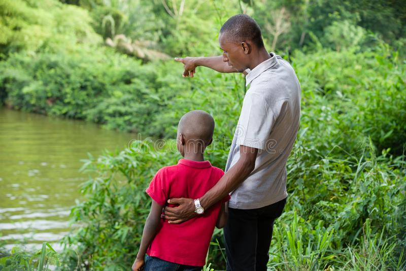Father and son relaxing together in the forest. Young father shows the importance of the river and the forest to his son stock photo