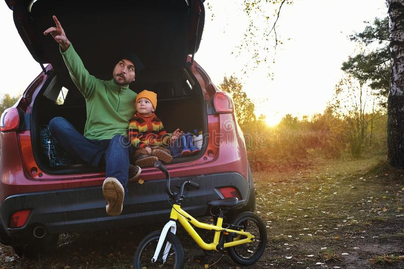 Father and son resting after day spending outdoor in autumn park, kid`s bicycle standing near. Dad and child sitting inside trunk stock image