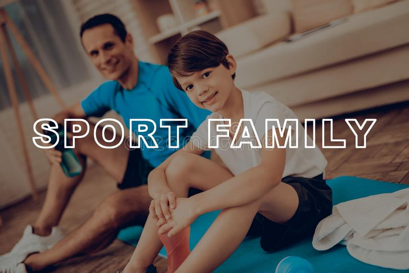 Father And Son Are Resting On The Gym Carpet. Healthy Lifestyle. Active Holiday. Sports Clothes. Working Out At Home. Bottles Of Water. Body Exercises. Family stock images