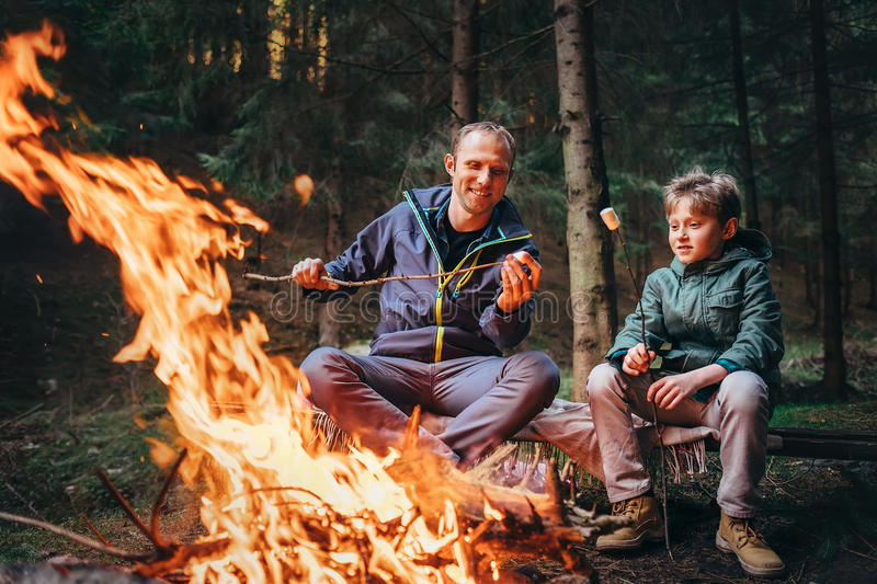 Father and son roast marshmallow candies on campfire royalty free stock images