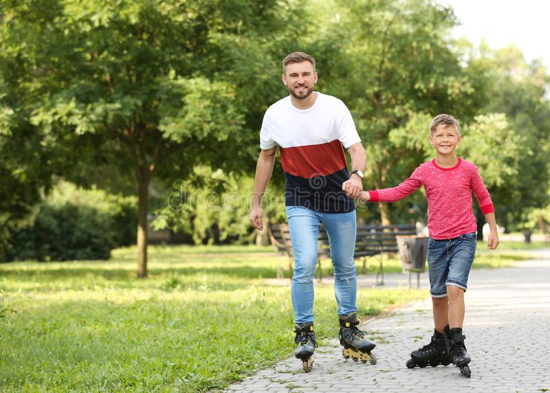 Father and son roller skating in park royalty free stock photo