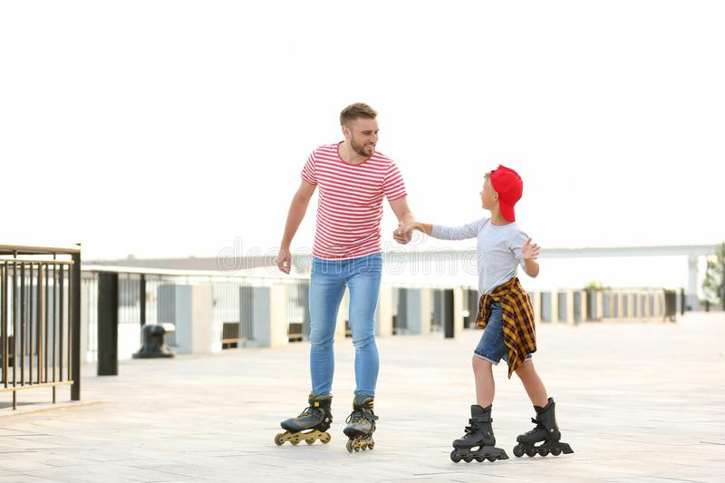 Father and son roller skating on street stock images