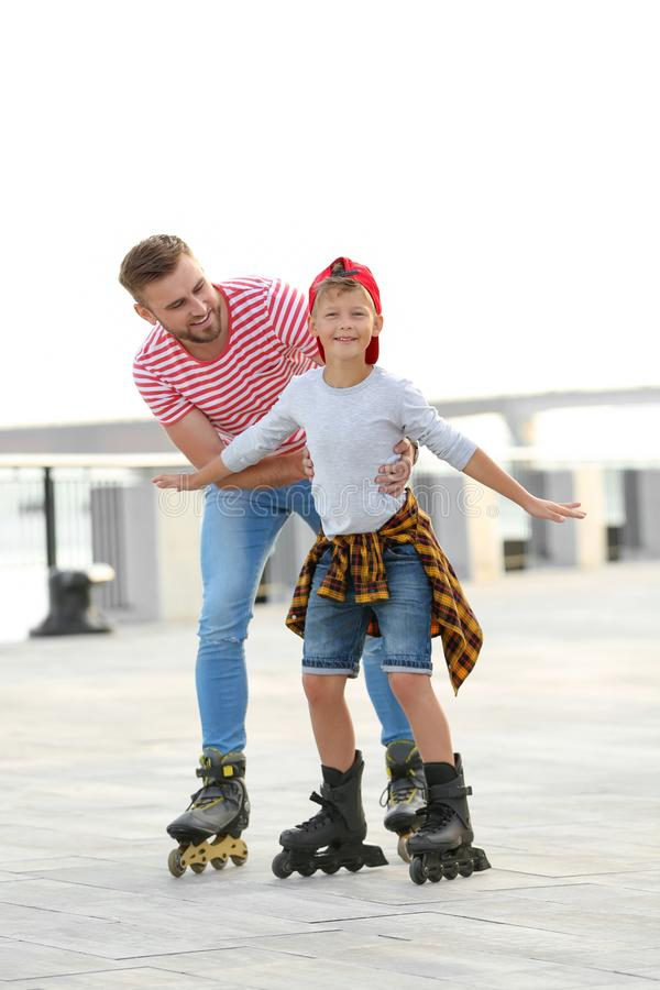 Father and son roller skating on street royalty free stock images