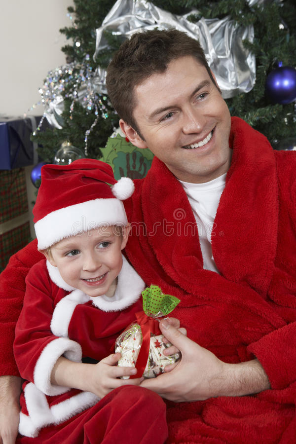 Father And Son In Santa Claus Outfit Holding Present. Happy Caucasian father and son in Santa Claus outfit holding Christmas gift stock image